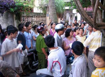 Hàng trăm người dân tụ tập trước cửa nhà hung thủ để cố được nhìn mặt gã chồng mất hết nhân tính.