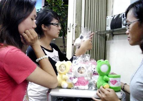 Nhiều bạn trẻ đang ngắm ngía những chú gấu bông hình mặt người. Ảnh: Tá Lâm.