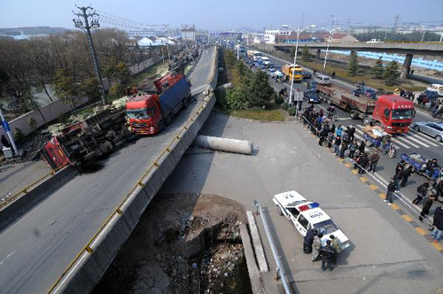 A policeman inspects a collapsed motorway viaduct in Shangyu of east China's Zhejiang Province, Feb. 21, 2011. The accident occurred early on Monday, with four trucks flipped over and three people injured
