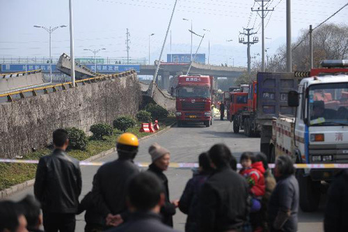 Onlookers behind guard lines watch the collapsed motorway viaduct in Shangyu of east China's Zhejiang Province, Feb. 21, 2011. The accident occurred early on Monday, with four trucks flipped over and three people injured