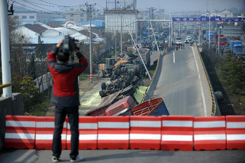 A cameraman shoots the collapsed motorway viaduct in Shangyu of east China's Zhejiang Province, Feb. 21, 2011. The accident occurred early on Monday, with four trucks flipped over and three people injured