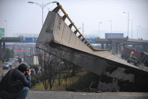 A photographer takes photos of the collapsed motorway viaduct in Shangyu of east China's Zhejiang Province, Feb. 21, 2011. The accident occurred early on Monday, with four trucks flipped over and three people injured