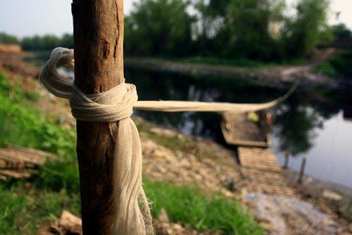 Một sợi dây lưới kết đôi, giăng cố định từ bờ này sang bờ kia sông Nhuệ.