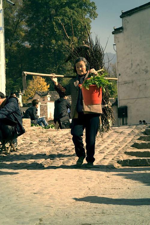Bà cụ đi kiếm củi, hái rau trở về nhà.