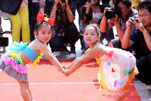 Hai cô bé cùng nắm tay nhau trình diễn thời trang.