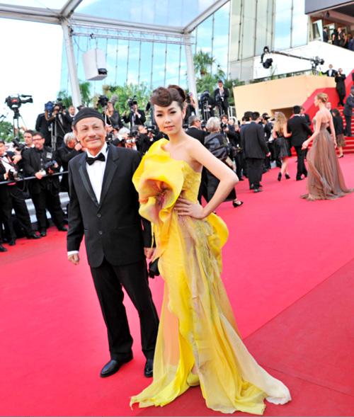 Minh Hằng chọn váy dạ hội cách điệu từ hình tượng hoa sen của nhà thiết kế Quỳnh Paris. Kiều nữ sải bước bên cạnh đạo diễn Lê Cung Bắc.