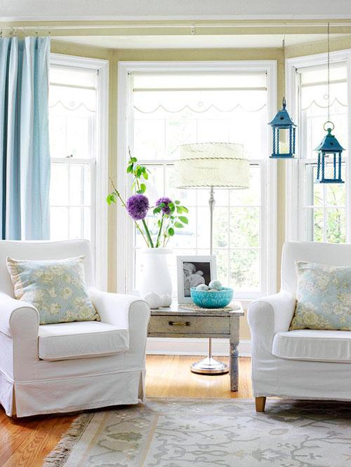 Phòng khách sáng sủa và mát mẻ nhờ cửa sổ kính rộng rãi, đồ đạc tông màu trắng.