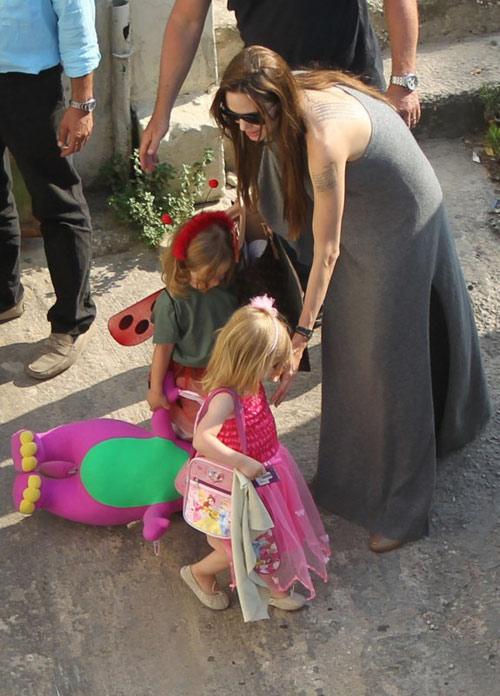 Bé Vivienne xinh xắn với váy hồng công chúa. Trong khi đó, Knox xách theo một con thú nhồi bông rất lớn.