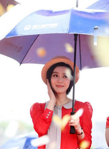 Băng Băng làm duyên trong nắng. Cô vừa đội mũ vừa che ô.