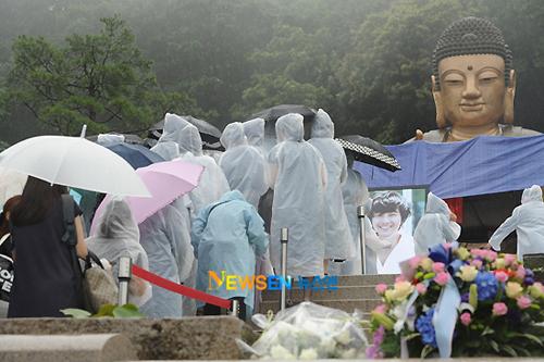 Dòng người liên tục đổ về nơi tổ chức lễ tưởng niệm, bất chấp trời mưa như trút.