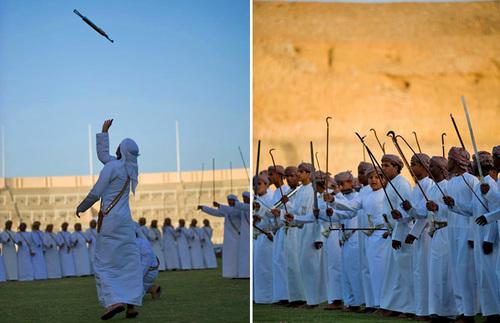 Những người đàn ông Oman mặc trang phục truyền thống đang chơi nhạc ngoài trời.