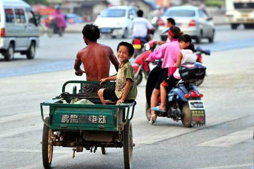 A 9-year-old boy named Xiong Sansan rides on the back of his father's tricycle to collect scraps in Baisha, an urban village in Liuzhou city, South China's Guangxi Zhuang autonomous region, July 29, 2011. The boy migrated to the city eight years ago with his parents, who maintain their tough lives by collecting scraps. During the summer vacation, Xiong always goes with his friends to the building site to collect scrap irons to contribute economically to his family. Even without a wide court, cool swimming pool, various summer camps or interest-oriented classes, Xiong and his friends can still find joy.