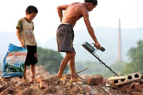 Xiong Sansan follows his father with a bag to collect scrap irons at a building site in Liuzhou city, South China's Guangxi Zhuang autonomous region, July 29, 2011
