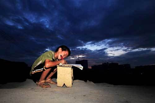 Xiong Sansan does his homework in Baisha, an urban village in Liuzhou city, South China's Guangxi Zhuang autonomous region, July 29, 2011