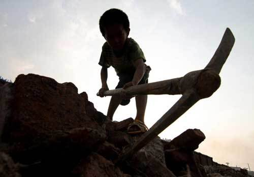 The 9-year-old, Xiong Sansan, digs scrap irons in an abandoned building site in Liuzhou city, South China's Guangxi Zhuang autonomous region, July 29, 2011