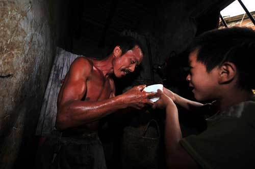 Xiong Sansan gives a bowl of water to his father who just came back from working in Baisha, an urban village in Liuzhou city, South China's Guangxi Zhuang autonomous region, July 29, 2011