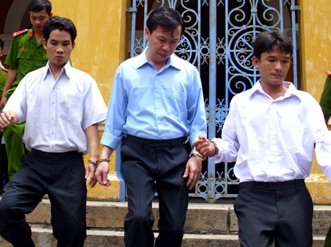 Phan Cao Trí (ở giữa) và đồng phạm bị dẫn ra xe tù. Ảnh: Tá Lâm.