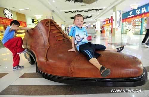 Bọn trẻ thích thú leo trèo lên chiếc giày để lái xe.