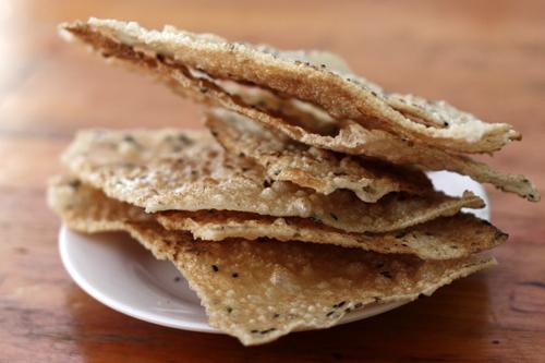 Bánh đa nướng giòn và được bẻ thành từng miếng khi ăn.
