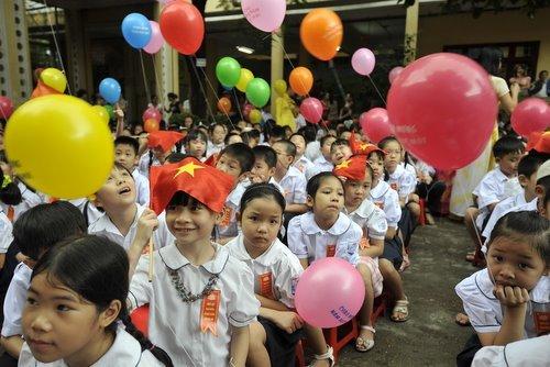 Khai giảng năm nay có mưa nhỏ, các em bé lấy cờ che mưa.