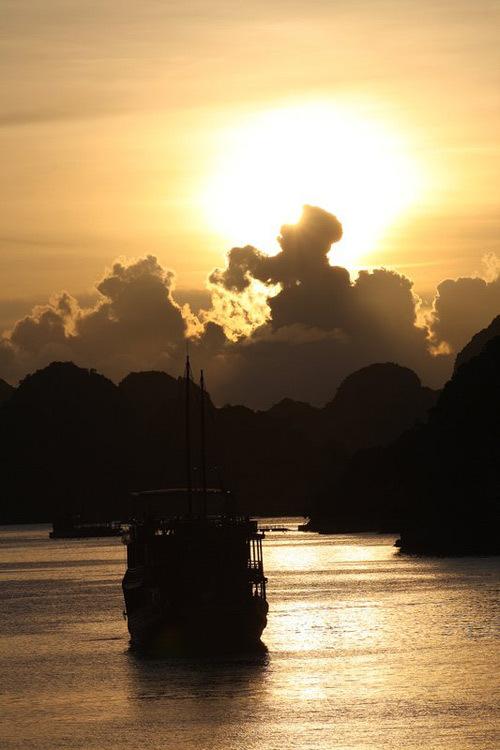 Con thuyền ra khơi trong ánh bình minh ở Hạ Long.