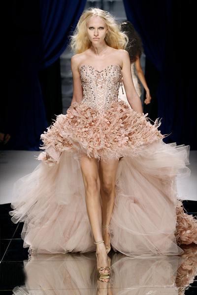 Váy cưới ngắn, có phần đuôi được làm bằng vải tuyn, phần trên đính hạt rất điệu đà, giúp bạn gái khoe đôi chân thon dài.