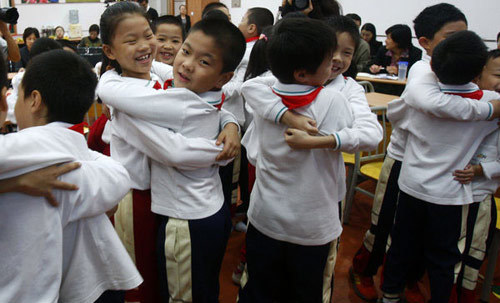 Students embrace each other in a sex education class at a primary school affiliated with the Shanghai University of Science and Technology, Oct 24, 2011