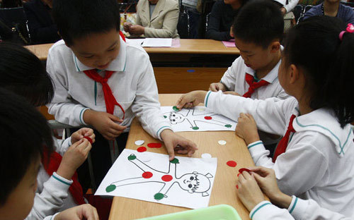 Students cover different parts of a cartoon human body with red or green pieces of paper during a lesson in sex education at a primary school affiliated with the Shanghai University of Science and Technology, Oct 24, 2011.