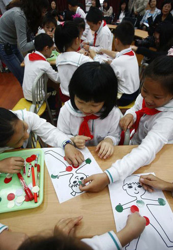 Students cover different parts of a cartoon human body with red or green pieces of paper during a lesson in sex education class at a primary school affiliated with the Shanghai University of Science and Technology, Oct 24, 2011