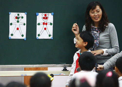 "A teacher teaches students in a sex education class called ""Traffic Lights for Our Bodies,"" at a primary school affiliated with the Shanghai University of Science and Technology, Oct 24, 2011. In the class, children are taught about their private parts, as well as how to protect themselves in accordance with rules described in the sex education book ""Boys and Girls."" This is the first sex education textbook to be introduced to pupils in Shanghai after numerous debates on early-childhood sex education in China. The book is expected to be introduced to students at 18 primary schools in the trial phase."