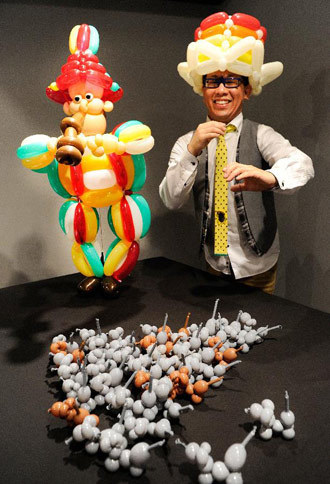 "Japan's balloon artist SHINO poses beside his works ""Snow White"" made of balloons during his exhibition with motifs of fairy tales in Tokyo on November 5, 2011."