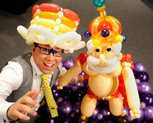 "Japan's balloon artist SHINO poses beside his works ""Jack and the Beanstalk"" made of balloons during his exhibition with motifs of fairy tales in Tokyo on November 5, 2011.("