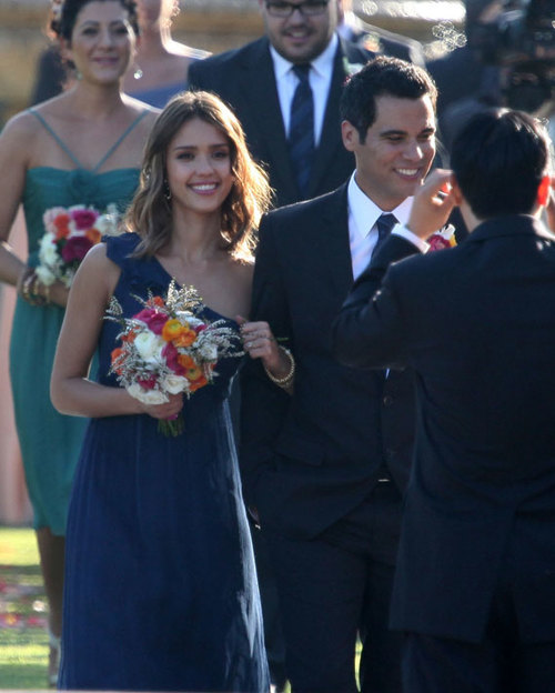 Jessica Alba mặc chiếc váy lệch vai hiệu Amsale khi làm phù dâu trong đám cưới một người bạn, bên cạnh chồng Cash Warren.