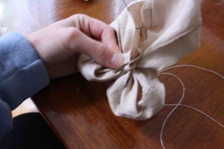 Sau khi đã khâu đường viền cho mảnh vải, cuộn mảnh vài dài vào thành 4 hoặc 5 cánh hoa theo kích thước mà bạn thích. Ban đầu cứ định dạng cánh hoa lại, sau đó bạn có thể chỉnh lại cho cân đối. Lật miếng vải lại phía sau, mỗi cánh hoa bạn hãy lấy kim chỉ khâu cố định lại.