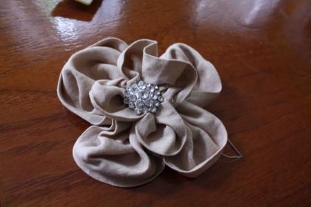 Dùng kim chỉ để gắn hai bông hoa lại với nhau, sau đó đặt chiếc nơ đính kim sa vào giữa.
