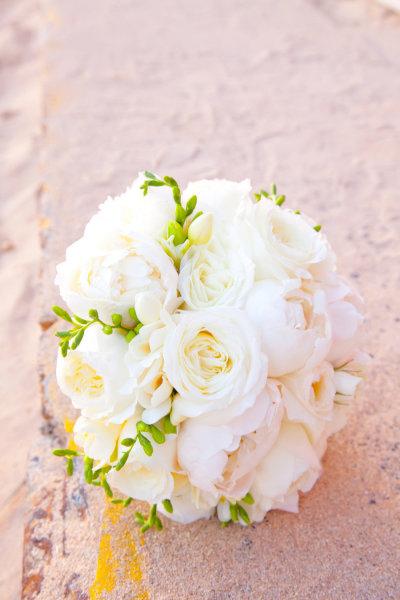 Hoa cầm tay của cô dâu được bó tròn đơn giản, hoa màu trắng nổi bật giữa các loại hoa nhiều màu khác.