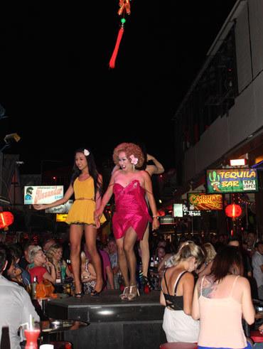 Bar ở đây thu hút khách bằng cách kê những bục biểu diễn ngoài trời như này. Các 'cô gái' trong ảnh thoải mái nhảy nhót và khoe ngực với khách đang uống bia bên dưới.
