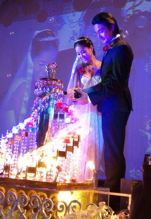 Cô dâu và chú rể làm lễ cắt bánh cưới trước sự tán thưởng của các khách mời. Gương mặt họ ngập tràn niềm hạnh phúc.