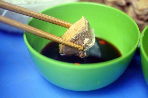 Chấm một ít xì dầu cho miếng thịt thêm đậm đà.