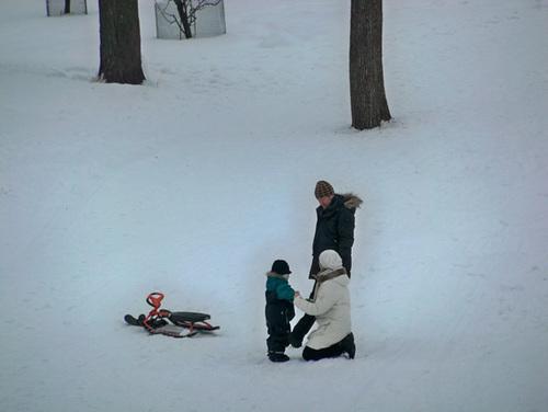 Em bé và cha mẹ giữa một vùng tuyết trắng.