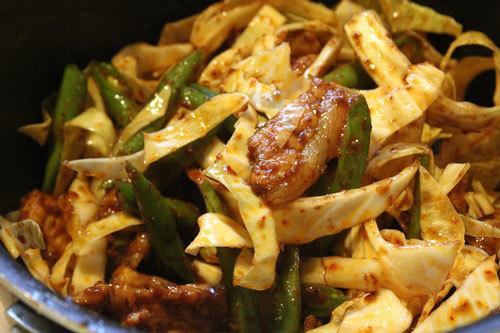 Cho tiếp bắp cải, đậu ve, lá chanh vào xào cùng thịt.