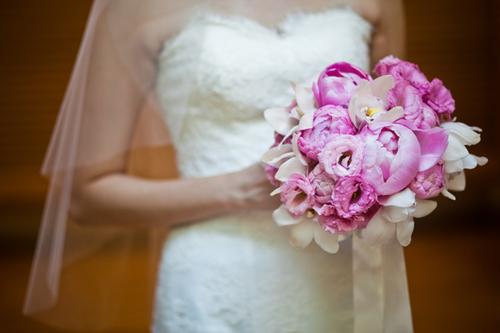 Bó hoa mẫu đơn hồng nổi bật với chiếc váy cưới trắng của cô dâu.