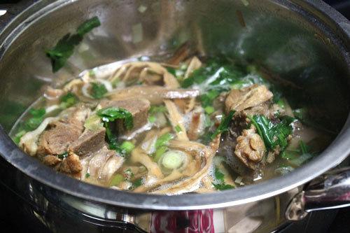 Canh chín cho hành lá, rau mùi vào, tắt bếp.