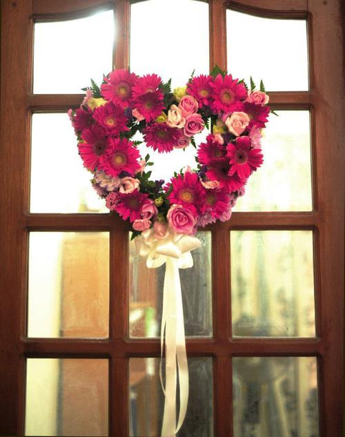 Trong lễ ăn hỏi, mọi người thường quan tâm tới phòng đón khách mà quên mất việc trang trí phòng cô dâu. Vì vậy, nhà tổ chức tiệc cưới đã chọn một chiếc vòng hoa hình trái tim màu hồng đậm để tô điểm cho cửa phòng.