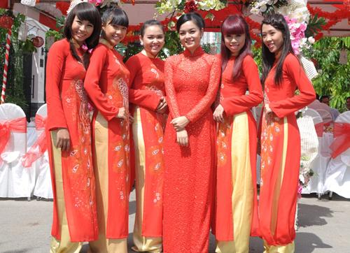 Đội bưng quả nữ diện áo dài đỏ thêu chim phượng và quần vàng, trong khi đó cô dâu Quỳnh Anh chọn chiếc áo đỏ cùng tông nhưng chất liệu cầu kỳ hơn.