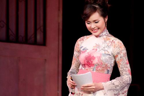 Trong chiếc áo dài đằm thắm, bà xã ca sĩ Lê Anh Dũng e thẹn cười duyên.
