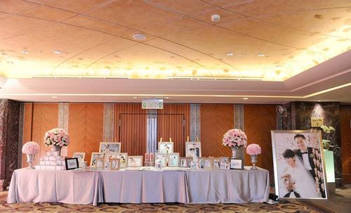 Tông màu chủ đạo: Đám cưới được trang trí bằng màu hồng với hai sắc thái đậm và nhạt, ngoài ra còn có các phụ kiện màu trắng. Ngay ở sảnh khách sạn, nhà tổ chức đã đặt một bàn đón tiếp với những bình hoa cao và những tấm ảnh lãng mạn của hai người.
