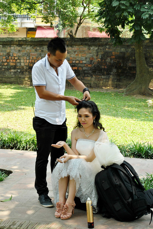 Stylist giúp cô dâu đổi kiểu tóc để tiếp tục thay đổi cảnh chụp khác.