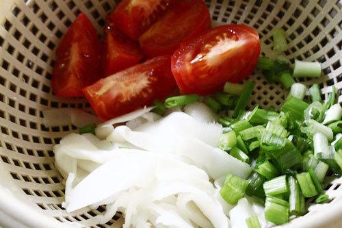 Cà chua bổ múi câu, măng xé sợi, hành lá thái nhỏ.