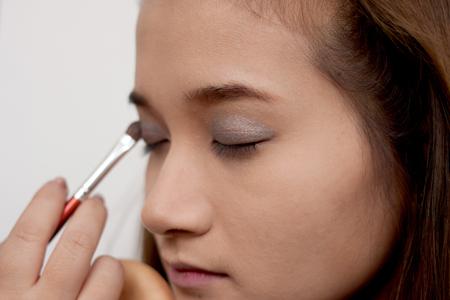 Đến bước trang điểm mắt, trước tiên, phủ phấn mắt màu xám lên toàn bộ bầu mắt trên